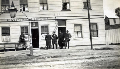 Men in suits outside of Empire Hotel