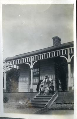 Man and four children and dog on house steps