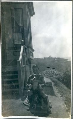 Boy and dog beside a house