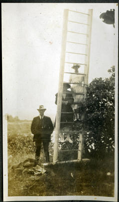 Man, with women posing on a ladder