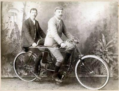 Two men on a Raleigh tandem bicycle.
