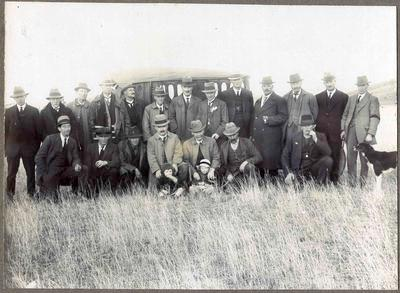 First Dog trials. A group of men with two small children and a sheep dog.