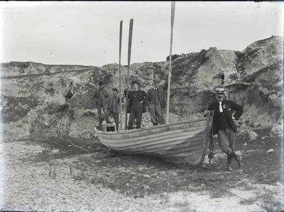 Brown Family standing in and around Old Oamaru Surfboat on beach at Kakanui, 1910