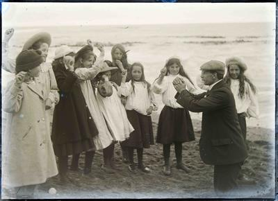 Unidentified man and girls on beach