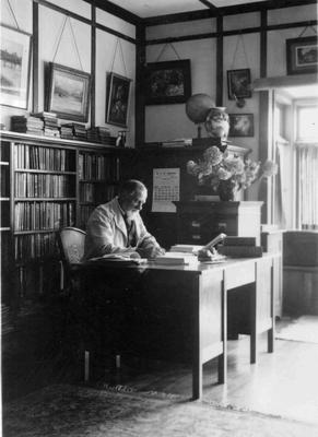 A C Gifford in the library of his home