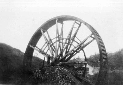 """Old Mill, Oamaru, 1937"". Picture of a mill wheel in a valley."