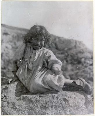 Young girl sitting on a rock; 2014/45.02.059