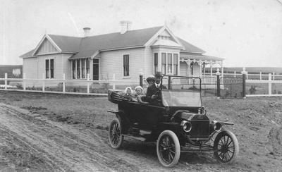 Model T ford and villa house, family