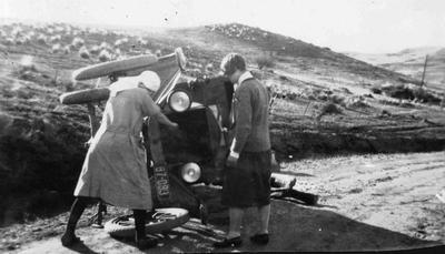 Car on its side with two ladies looking on