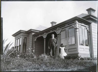 Man and child in front of house. Unidentified