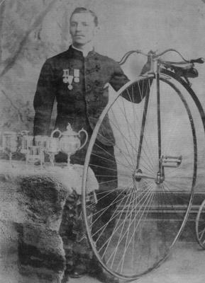 John Edmond Hood, Watchmaker and Jeweller, with Penny Farthing and Cups.
