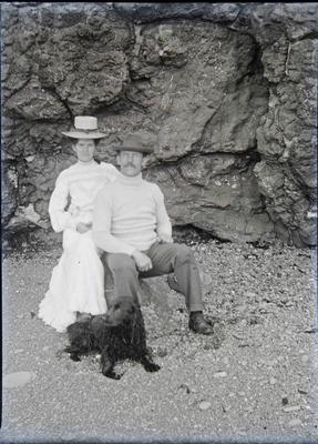 Male and female with dog at beach