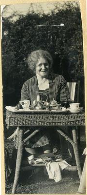 Unidentified woman having tea in a garden; 2014/45.01.024
