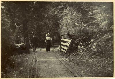 Man and woman walking along a road; 2014/45.01.040