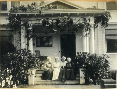 Four women sitting on house steps; 2014/45.01.119