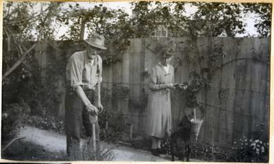 Man, woman and dog in a garden.; 2014/45.01.266