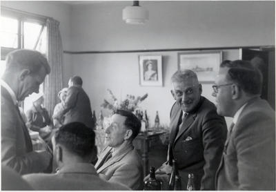 Five men in conversation, two women seated in background.