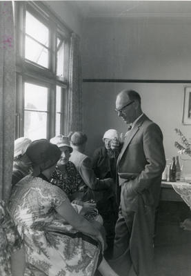 A group of women and one man conversing.