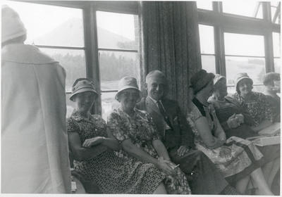 A group of women and Tom Sheat seated at an afternoon tea.
