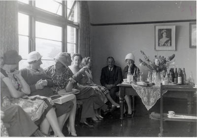 A group of women and two men at afternoon tea.