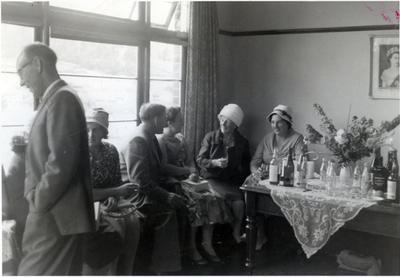 A group of women and two men at afternoon tea including Mrs Bevis, and W. Matheson.
