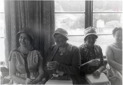Four women, each holding drinks.