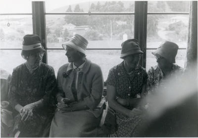 Four seated women in conversation.