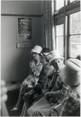 Four seated women wearing hats.