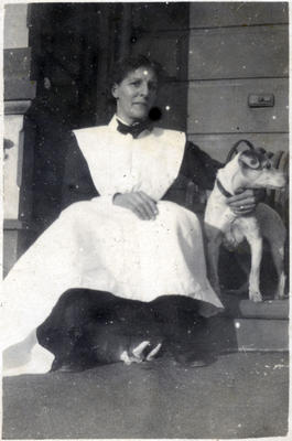 Woman sitting on a porch with a dog.; 2014/43.2.86