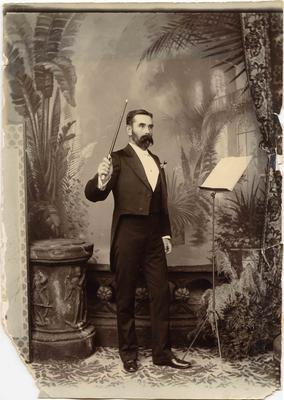 A man dressed in formal attire holding a conductor's baton.