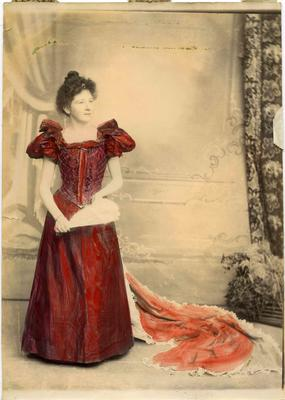 A young woman in a full length gown with a train, also holding a fan.