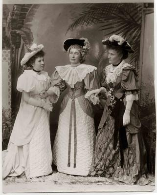 Three young women dressed in elaborate  Victorian day costume.