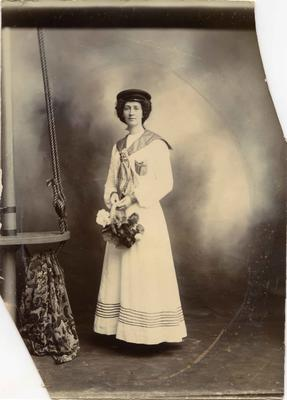 A young woman in a long skirt with a sailor's style blouse and cap.
