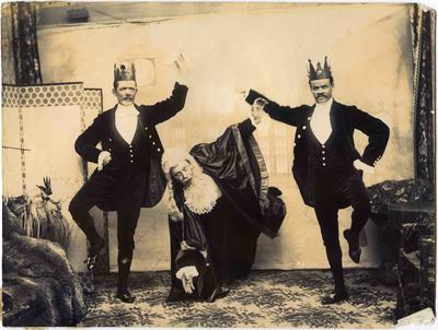 Three male theatrical characters. One a judge, the other two servants wearing crowns.