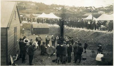 A brass band performing out of doors. A large crowd standing in the background.