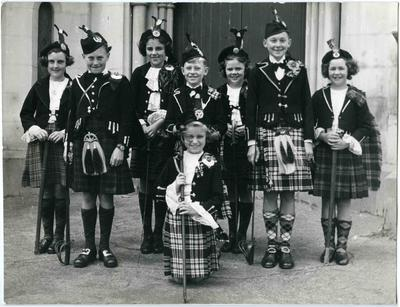 A group of eight children in Highland dance costume.