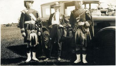 Three men, two in Highland Pipe Band uniform.
