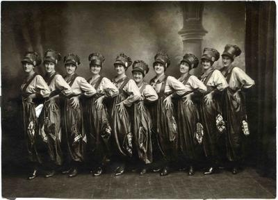 Ten young women in theatrical costume.