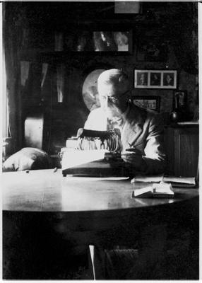 Unidentified man using an early typewriter.