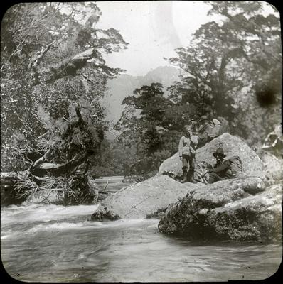 Three men beside a river
