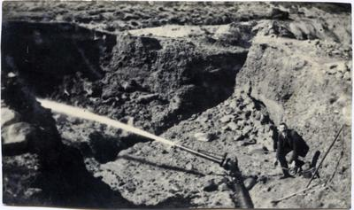 Man with a sluicing gun. Gold mining.