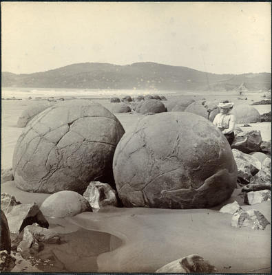 Woman beside boulders on Moeraki Beach.