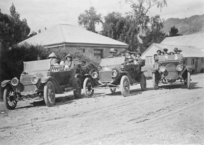 Unidentified family outing in motor cars