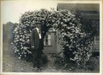 Unidentified man with archway of flowers
