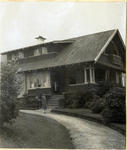 Unidentified woman in front of a house