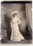Young woman in full length gown and feathered hat.