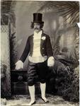 A man dressed in elaborate early Victorian costume with a top hat.