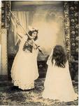 A young woman in full length costume preparing to stab a person who is kneeling.