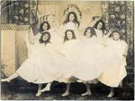 Seven young women dressed in white taking part in a dance routine.