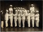Sixteen young women in sailor costume.